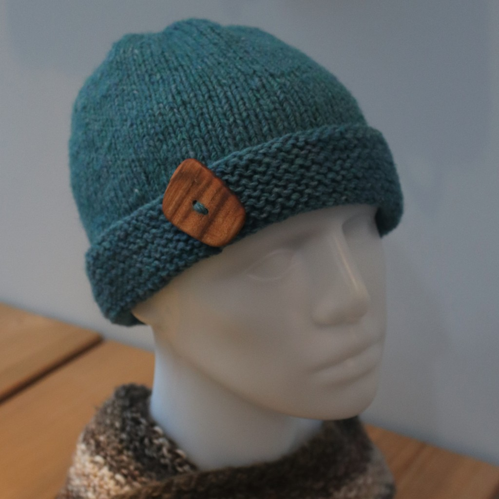 Blue knit beanie hat with wooden button on garter stitch brim, modeled on a plastic head manequin.
