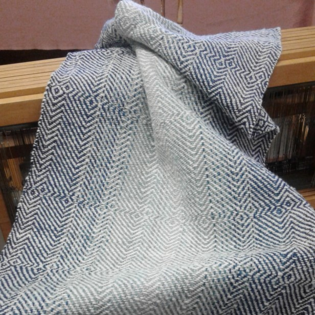 woven blue and white twill shawl draped over a wooden weaving loom