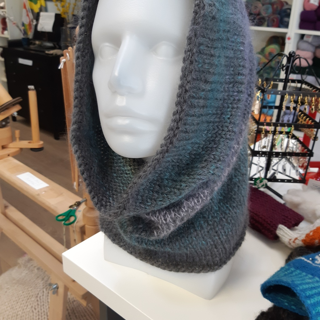 grey mohair and wool cowl pulled up onto the top of the head of a plastic head manequin