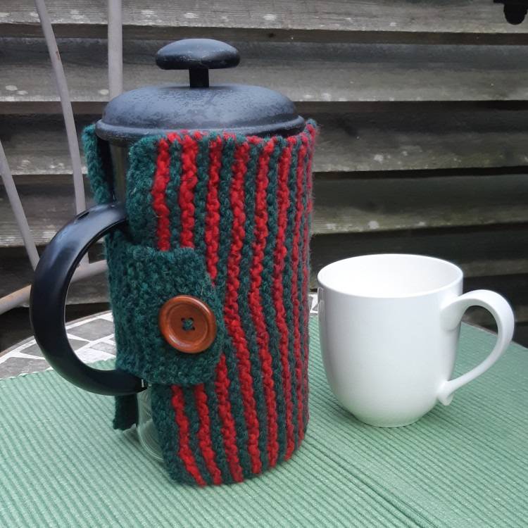 Green and red striped garter stitch rectangle with a wood button surrounding a French Press coffee maker with a cream mug beside.