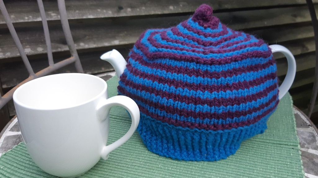 mug and teapot on green placemat. Teapot has a blue and purple striped tea cozy.