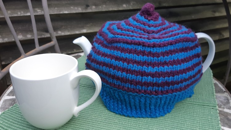 White mug and tea pot on green placemat. Tea pot has a blue and purple striped knit cozy.